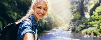 Lächelnde Frau in der Natur mit Bach im Hintergrund
