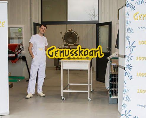 Mitarbeiter von Genusskoarl neben Firmenlogo in Betriebshalle